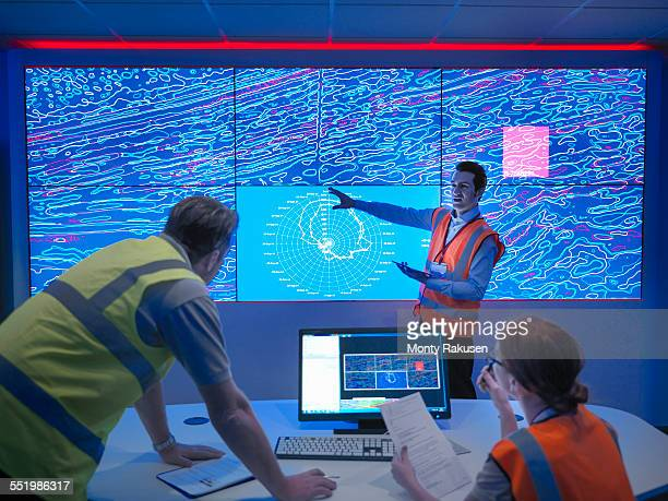 Geologists studying graphical display of oil and gas bearing rock on screens
