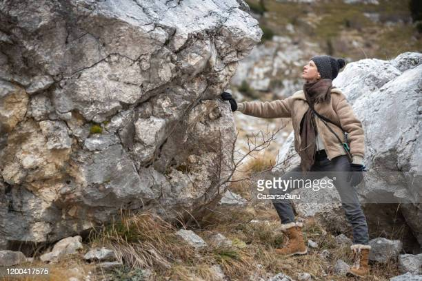 geology enthusiast examining boulder in mountains - stock photo - geologia imagens e fotografias de stock