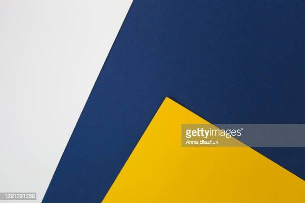 geometric abstract paper background of blue, yellow and white colors. trendy modern flat lay. - ツートンカラー ストックフォトと画像