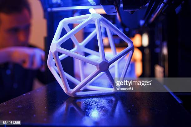 3D geometric figure on the platform of a 3D printer with a man in the background