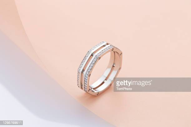 geometric shape silver ring with diamonds on pink background - white gold stock pictures, royalty-free photos & images