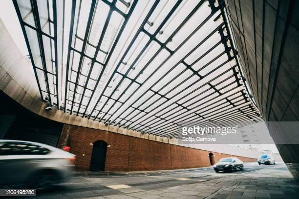 geometrical building and fast moving cars in big city - road junction stock pictures, royalty-free photos & images