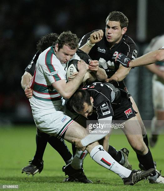 Geordan Murphy of Leicester is tackled by Thomas Castaignede and Ben Johnston during the Guinness Premiership match between Saracens and Leicester...