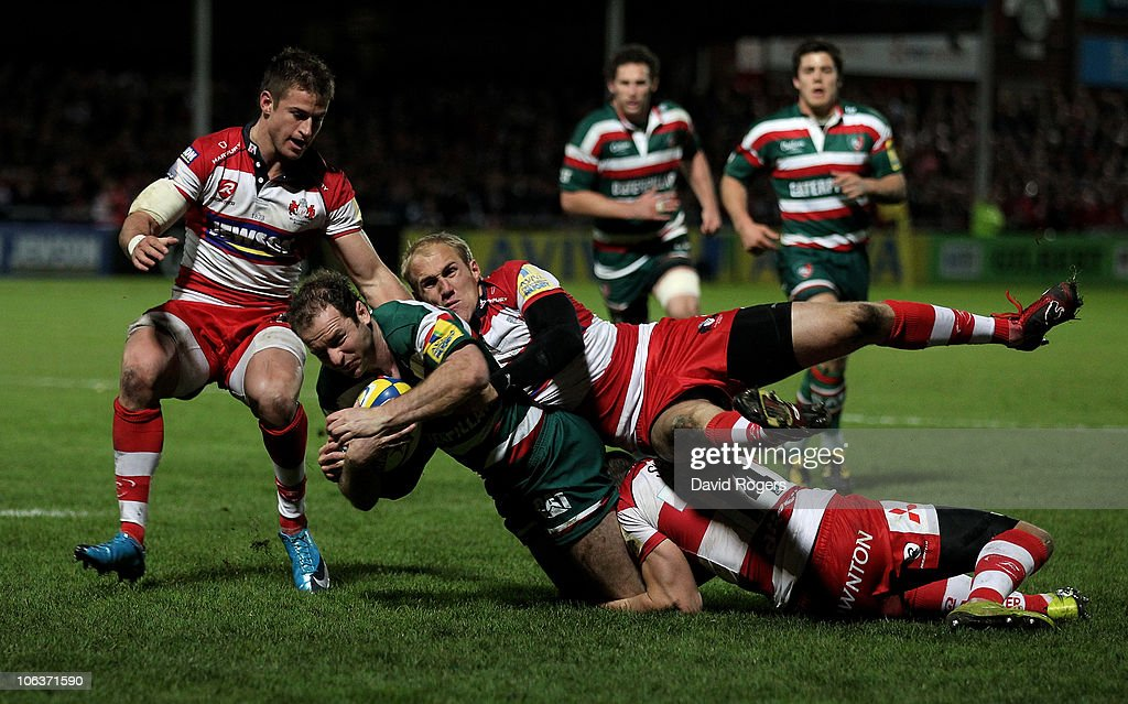 Geordan Murphy of Leicester Tigers is tackle by Olly Morgan, Charlie Sharples (R) and Henry Trinder during the Aviva Premiership match between Gloucester and Leicester Tigers at Kingsholm on October 30, 2010 in Gloucester, England.