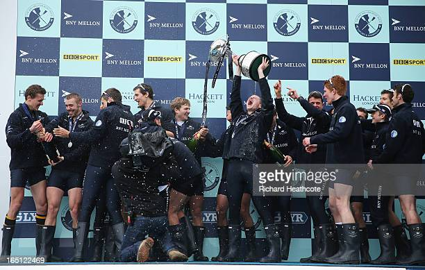 Geordie Macleod of Oxford lifts the trophy as team mates celebrate after the BNY Mellon 159th Oxford versus Cambridge University Boat Race on The...