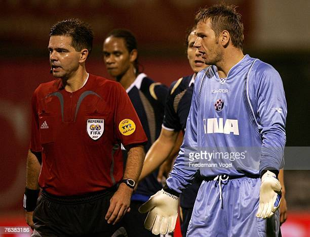 Georg Koch of Zagreb speaks with Referee Terje Hauge during the Champions League third qualifying round second leg match between Dinamo Zagreb and...