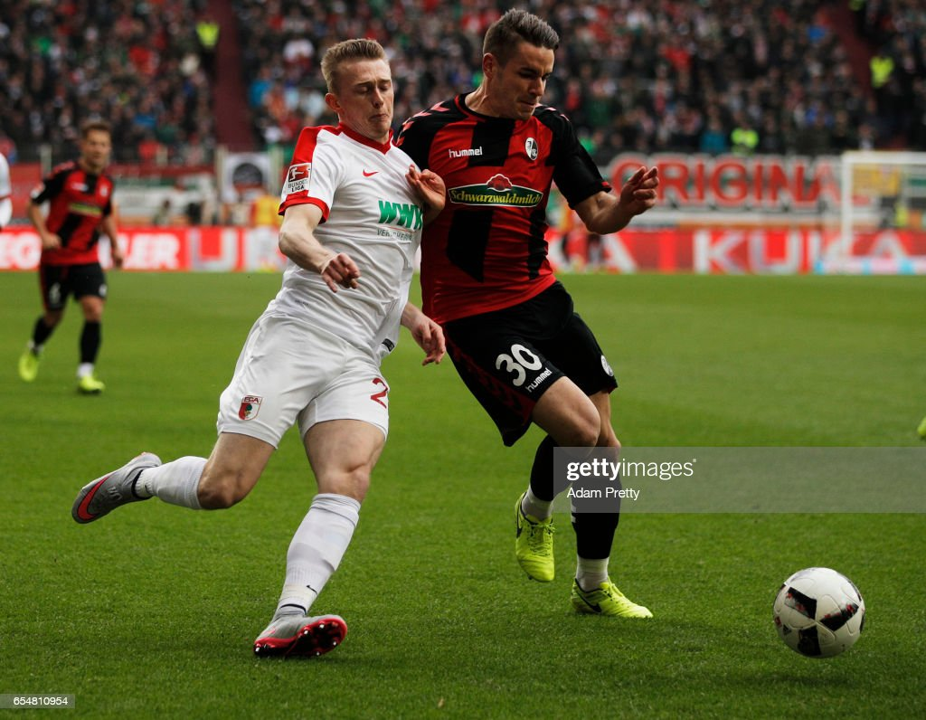 Georg Teigl of Augsburg is challenged by Christian Guenter of Freiburg during the Bundesliga match between FC Augsburg and SC Freiburg at WWK Arena on March 18, 2017 in Augsburg, Germany.