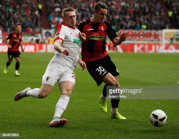 Georg Teigl of Augsburg is challenged by Christian Guenter of Freiburg during the Bundesliga match between FC Augsburg and SC Freiburg at WWK Arena...
