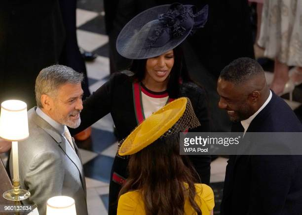 George and Amal Clooney talk to Idris Elba and Sabrina Dhowre in St George's Chapel at Windsor Castle for the wedding of Prince Harry and Meghan...