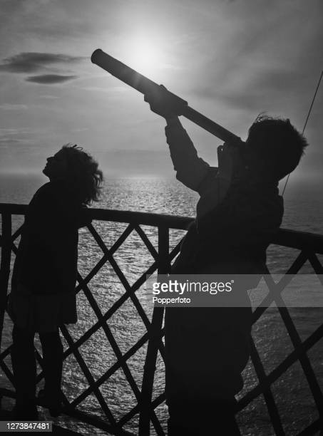 George and Mary Howarth children of the resident lighthouse keeper use a telescope to view passing aircraft on patrol duties from the tower of the...