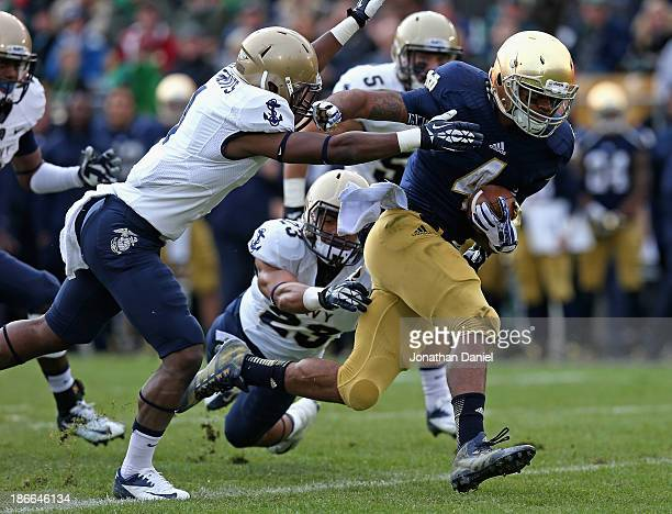George Atkinson III of the Notre Dame Fighting Irish breaks away from Chris Feruson and Brandon Clements of the Navy Midshipmen to score a touchdown...