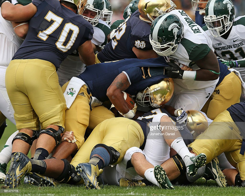 George Atkinson III #4 of the Notre Dame Fighting Irish is stopped by the members of the Michigan State Spartan defense including Micajah Reynolds #60 at Notre Dame Stadium on September 21, 2013 in South Bend, Indiana.