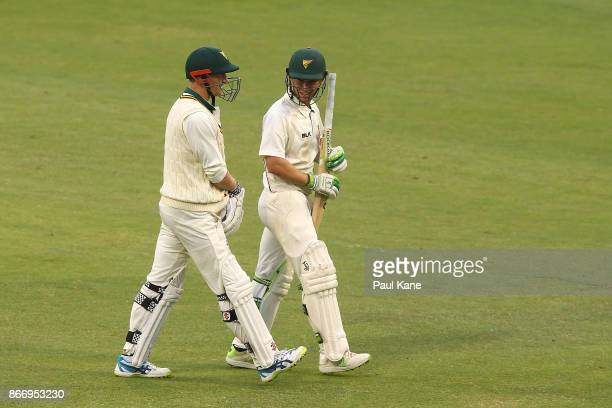 George Bailey and Jake Doran of the Tigers walk from the field after the umpires called for the covers due to light showers during day two of the...