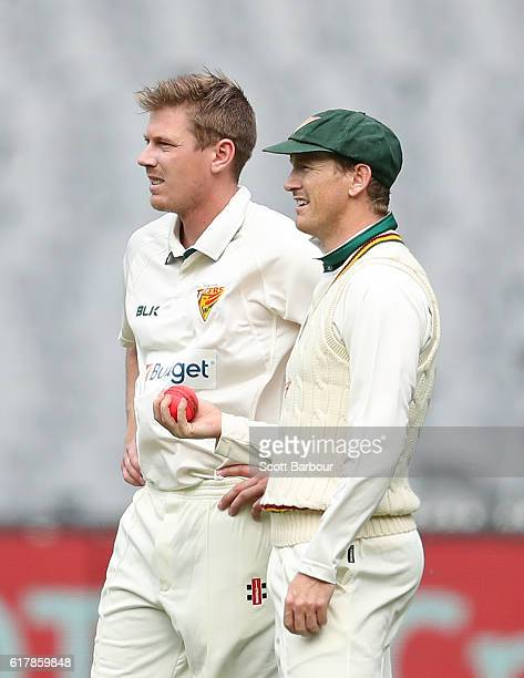 George Bailey captain of Tasmania speaks with bowler James Faulkner of Tasmania during day one of the Sheffield Shield match between Victoria and...