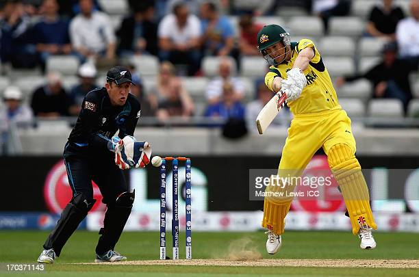 George Bailey of Australia hits the ball towards the boundary as Luke Ronchi of New Zealand looks on during the ICC Champions Trophy Group A match...