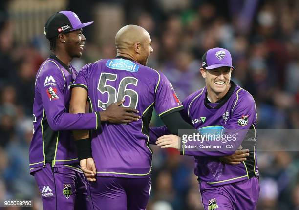 George Bailey of the Hurricanes celebrates with Jofra Archer and Tymal Mills after taking a catch to dismiss Brendon McCullum of the Heat during the...