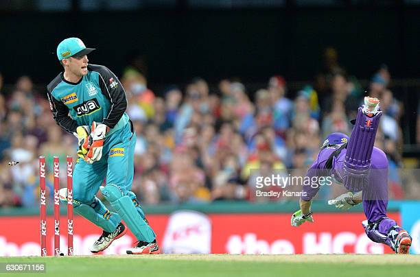 George Bailey of the Hurricanes is caught short of his ground by wicketkeeper Jimmy Peirson of the Heat during the Big Bash League between the...