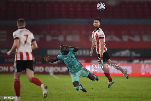 George Baldock of Sheffield United battles for a header with Sadio Mane of Liverpool during the Premier League match between Sheffield United and...