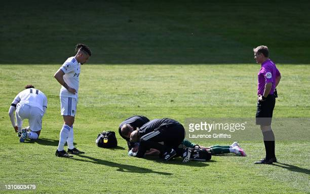George Baldock of Sheffield United receives medical treatment as Kalvin Phillips of Leeds United looks on during the Premier League match between...