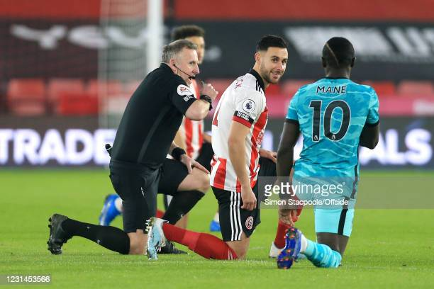 George Baldock of Sheffield United smiles at Sadio Mane of Liverpool as they take the knee alongside referee Jon Moss in support of the Black Lives...
