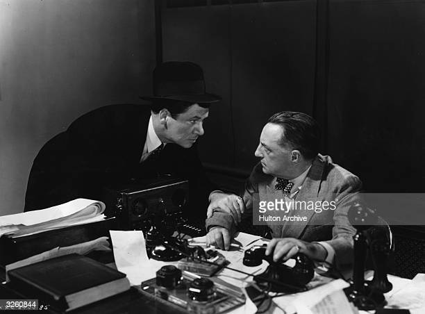 George Bancroft a burly American actor who generally played tough or villainous roles leans urgently over a desk in a scene from the film 'Blood...