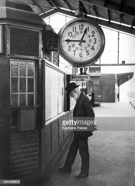 George Bernard SHAW consulting the notice board in Berlin Friedchstrasse Station at 12.45 pm one day between 1930 and 1939 while waiting for his...