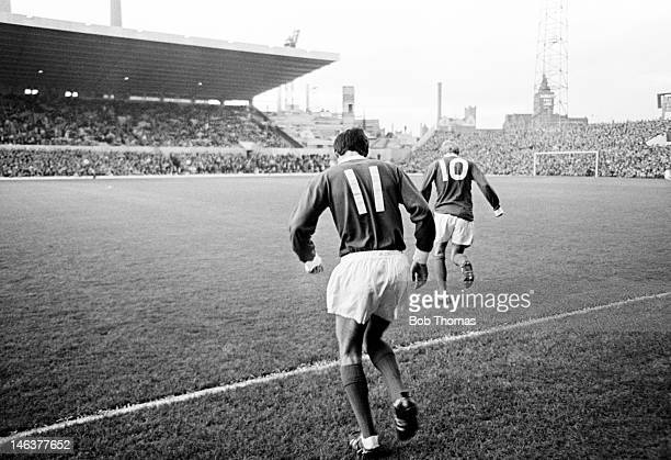 George Best of Manchester United runs onto the pitch following Denis Law at Old Trafford circa 1964