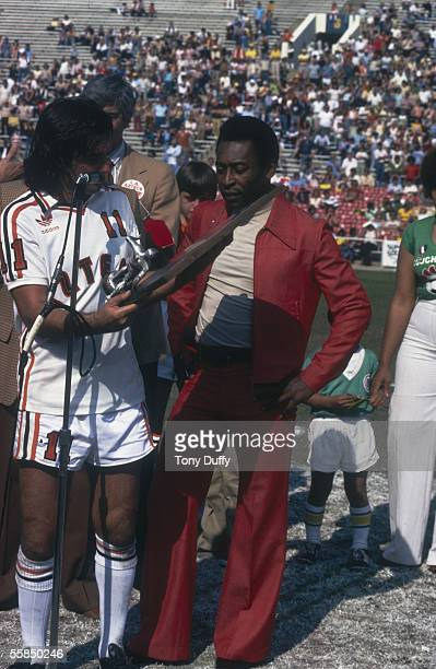 George Best of the LA Aztecs is presented a trophy by Pele of the New York Cosmos before the NASL League match between the New York Cosmos and LA...