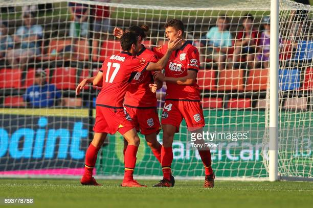 George Blackwood of Adelaide celebrates a goal with a team mates during the round 11 ALeague match between the Newcastle Jets and the Adelaide United...