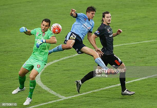 George Blackwood of Sydney FC competes for the ball against Roar goalkeeper Michael Theo and James Donachie of the Roar during the round 17 ALeague...