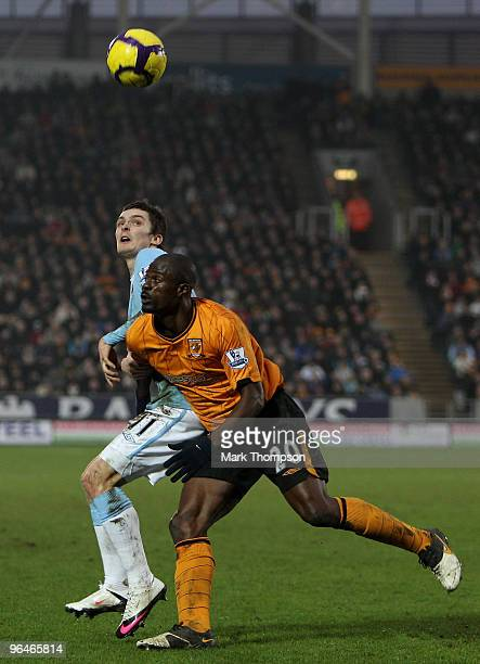 George Boateng of Hull City tangles with Adam Johnson of Manchester City during the Barclays Premier League match between Hull City and Manchester...