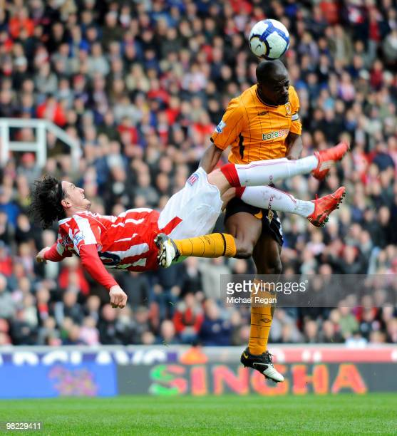 George Boateng of Hull clears the ball before being kicked in the head by Tuncay of Stoke during the Barclays Premier League match between Stoke City...