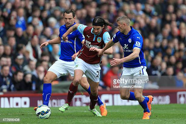 George Boyd of Burnley battles with Daniel Drinkwater and Paul Konchesky of Leicester during the Barclays Premier League match between Burnley and...
