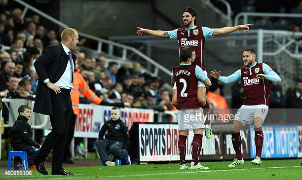 George Boyd of Burnley is lifted up after scoring the third Burnley goal as manager Sean Dyche looks on during the Barclays Premier League match...