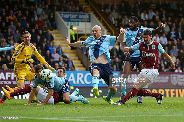 George Boyd of Burnley shoots past James Collins of West Ham to score his team's first goal during the Barclays Premier League match between Burnley...