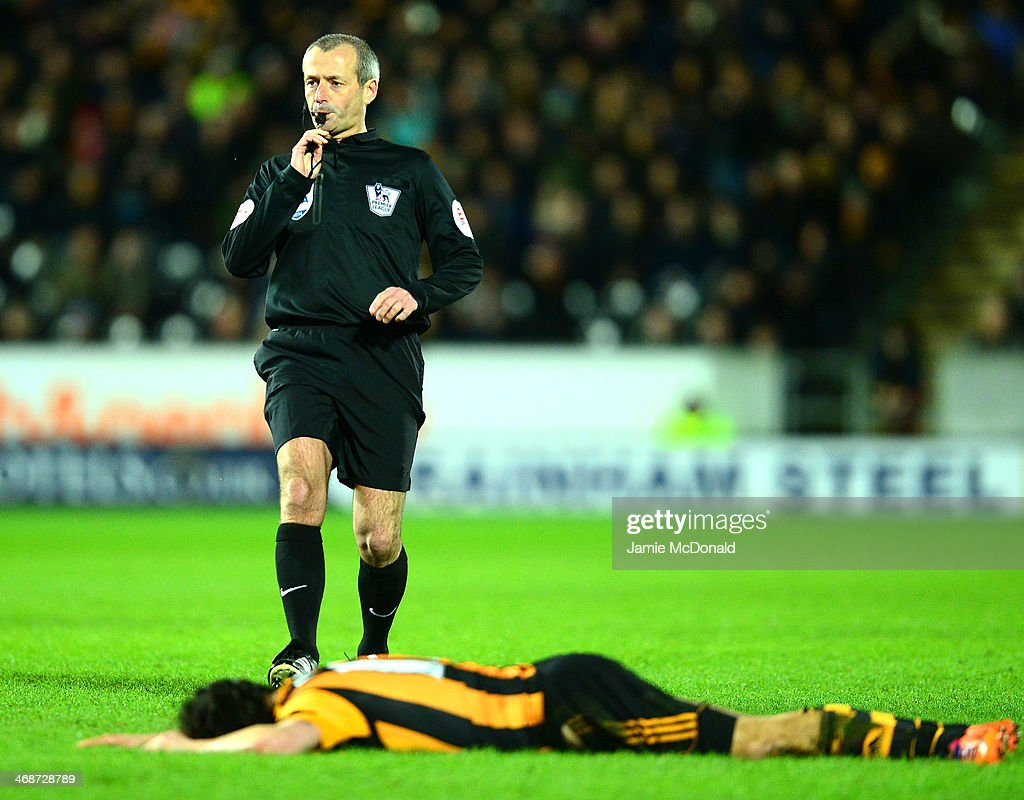 George Boyd of Hull City lies on the pitch as Referee Martin Atkinson blows his whistle uring the Barclays Premier League match between Hull City and Southampton at the KC Stadium on February 11, 2014 in Hull, England.