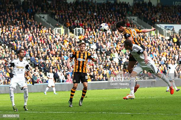 George Boyd of Hull City rises above Angel Rangel of Swansea to score the opening goal with a header during the Barclays Premier league match between...