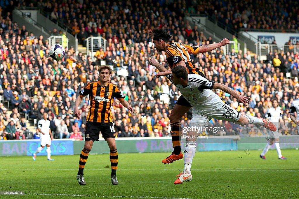 George Boyd of Hull City rises above Angel Rangel of Swansea to score the opening goal with a header during the Barclays Premier league match between Hull City and Swansea City at KC Stadium on April 5, 2014 in Hull, England.
