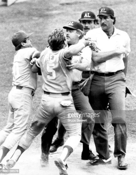George Brett of the Kansas City Royals is restrained by umpire Joe Brinkman and manager Dick Howser as he tries to get to home plate umpire Tim...