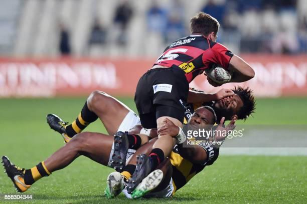 George Bridge of Canterbury is tackled by Manasa Mataele of Taranaki and Seta Tamanivalu of Taranaki during the round eight Mitre 10 Cup match...