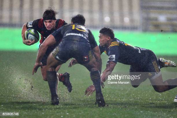 George Bridge of the Crusaders slips through the tackle of Waisake Naholo of the Highlanders during the Super Rugby Quarter Final match between the...