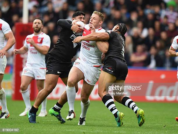 George Burgess of England is tackled by Jason Taumalolo and Martin Taupau of New Zealand Kiwis during the Four Nations match between the England and...