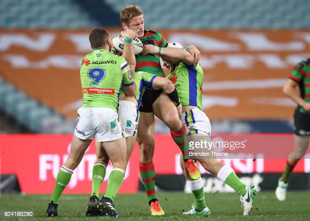 George Burgess of the Rabbitohs is tackled by the Raiders defence during the round 21 NRL match between the South Sydney Rabbitohs and the Canberra...