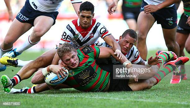 George Burgess of the Rabbitohs scores a try in the tackle of Kane Evans and Roger Tuivasa Sheck of the Roosters during the round two NRL match...