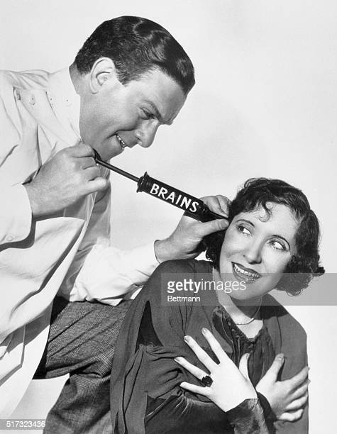 George Burns playfully injects a syringe marked 'Brains' into the ear of Gracie Allen his wife and comedy partner Burns said 'This won't hurt a bit...