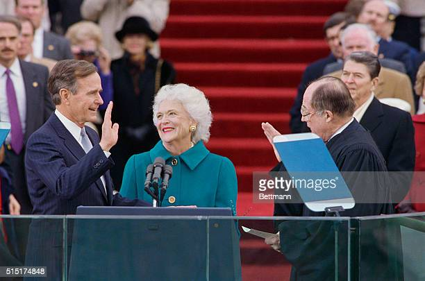 George Bush is being sworn in while wife Barbara looks on lovingly Standing in background in Ronald Reagan