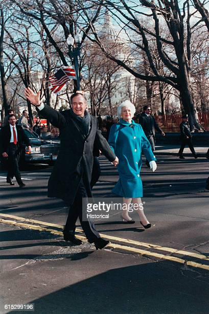 George Bush smiles and waves onlookers as he and Barbara walk down a street on his inauguration day Washington DC January 20 1989