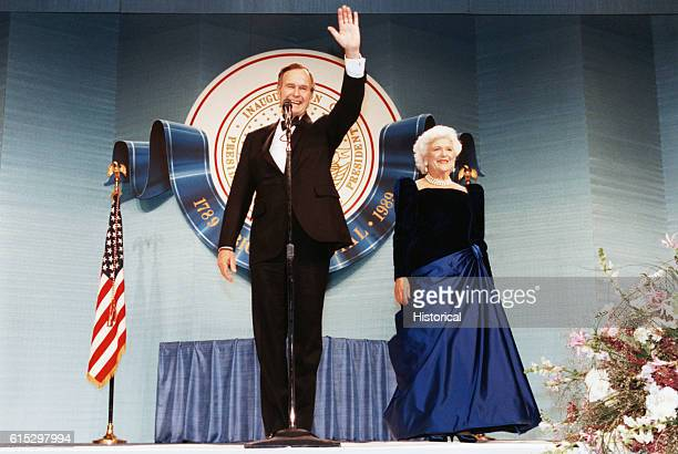 George Bush smiles and waves to participants of his inaugural celebration as Barbara looks on Washington DC January 20 1989