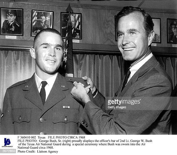 George Bush Sr proudly displays the officer's bar of 2nd Lt George W Bush from the Texas Air National Guard during the ceremony in which the younger...