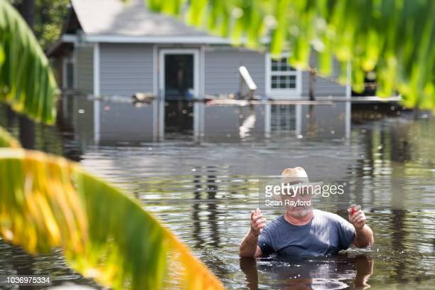 George Butler walks through floodwaters in his backyard caused by Hurricane Florence on September 20, 2018 in Longs, South Carolina. Floodwaters are...